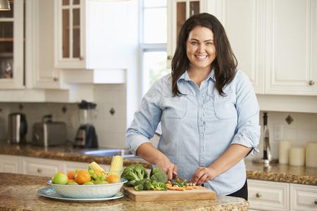 Sovrappeso donna preparando le verdure in cucina Archivio Fotografico - 33514904