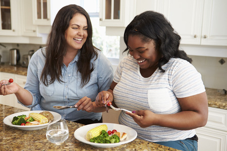 Two Overweight Women On Diet Eating Healthy Meal In Kitchen photo
