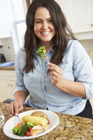 Overweight Woman Eating Healthy Meal In Kitchen Stock Photo