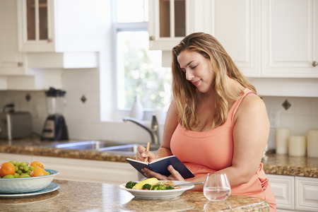 Overweight Woman On Diet Keeping Food Journal