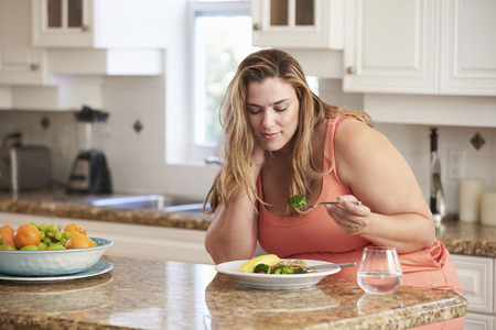 obesity: Overweight Woman Eating Healthy Meal In Kitchen Stock Photo
