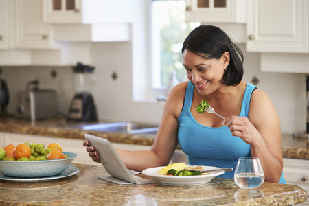 fat food: Overweight Woman With Digital Tablet Checking Calorie Intake