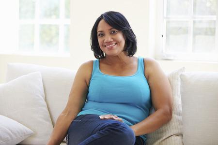 mujeres maduras: Retrato de mujer con sobrepeso sentado en el sofá