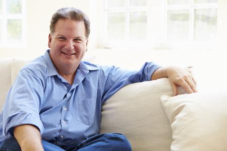hombres maduros: Retrato De Sobrepeso hombre sentado en el sofá Foto de archivo