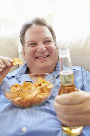 male age 40's: Overweight Man At Home Eating Chips And Drinking Beer