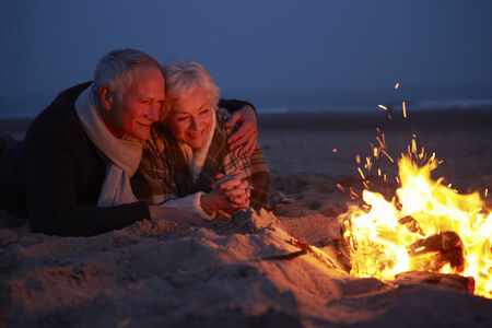 winter couple: Senior Couple Sitting By Fire On Winter Beach