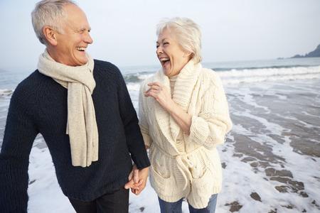 Anziano coppia a piedi lungo la spiaggia di inverno Archivio Fotografico - 33518916