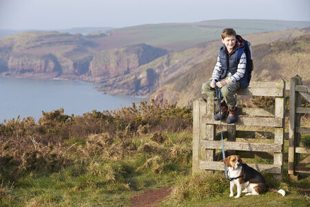 Boy With Dog Walking Along Coastal Path Stock Photo