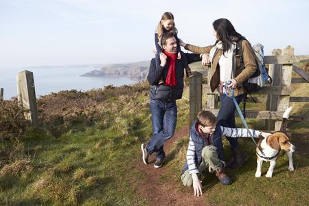 Family With Dog Walking Along Coastal Path photo