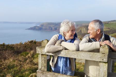 海岸のパスに沿って歩く年配のカップル