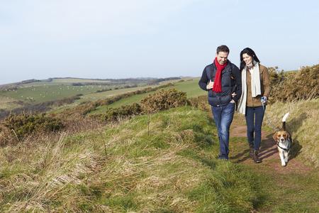 parejas caminando: Pares con el perro recorren a lo largo ruta costera