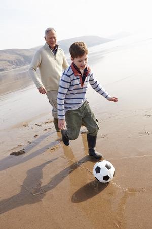 祖父と孫の冬の浜辺でサッカー