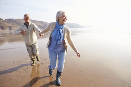 冬のビーチに沿って実行している年配のカップル