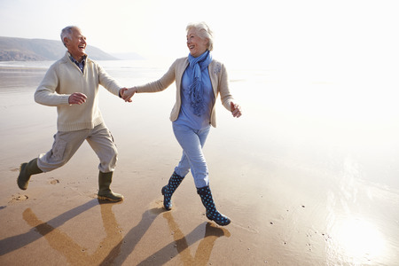 Senior Couple Running Along Winter Beach Stock Photo