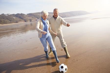 Coppie maggiori giocare a calcio sulla spiaggia di inverno