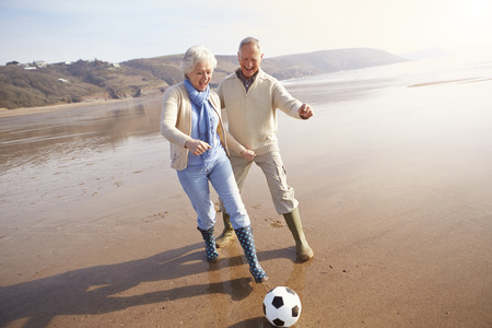 Having Fun: Senior Couple Playing Football On Winter Beach