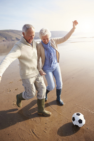 active: Senior Couple Playing Football On Winter Beach