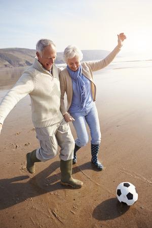 scarf beach: Senior pareja jugando al f�tbol en la playa de invierno Foto de archivo