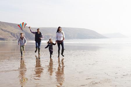 Familia que se ejecuta a lo largo de la playa de invierno Vuelo de la cometa