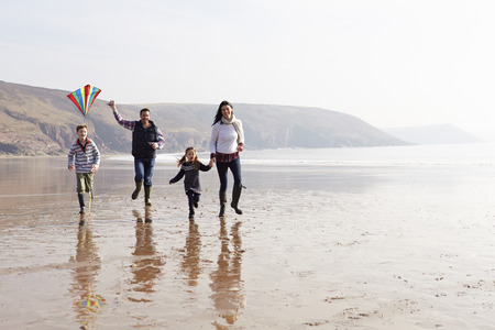 healthy person: Family Running Along Winter Beach Flying Kite