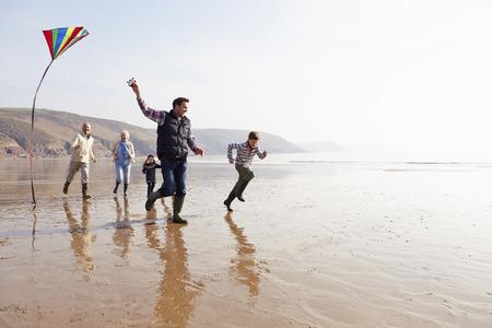 familias unidas: Multi generacional Vuelo de la cometa en la playa del invierno Foto de archivo