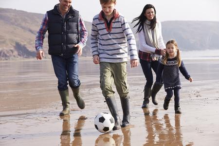 Family Playing Football On Winter Beach photo