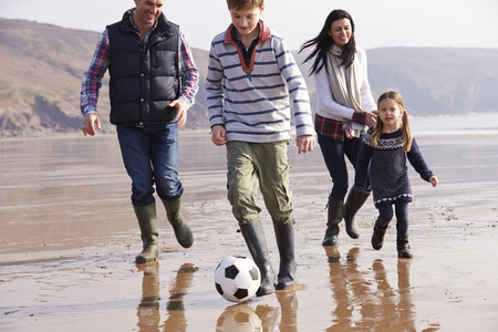 Family Playing Football On Winter Beach photo