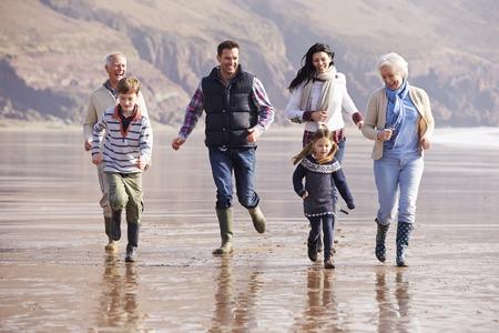 Multi-generatie familie Running On Winter Beach Stockfoto