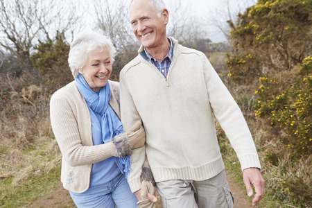 Senior Couple Walking Through Winter Countryside photo