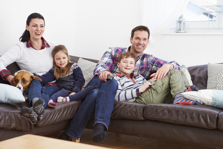 indoors: Family Relaxing Indoors Watching Television Together Stock Photo