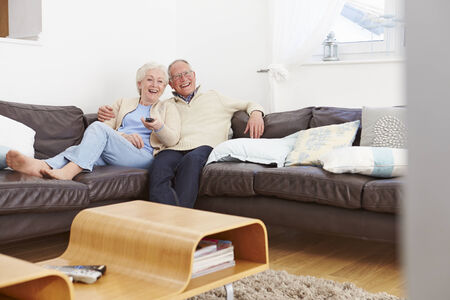 couple couch: Senior Couple Sitting On Sofa Watching TV