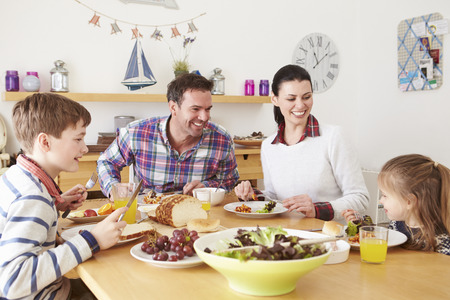 Familia come el almuerzo en la tabla de cocina