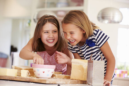 7 years old: Girls Eating Ingredients Whilst Making Cheese On Toast Stock Photo