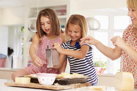 母は、トーストにチーズを作る女の子 写真素材