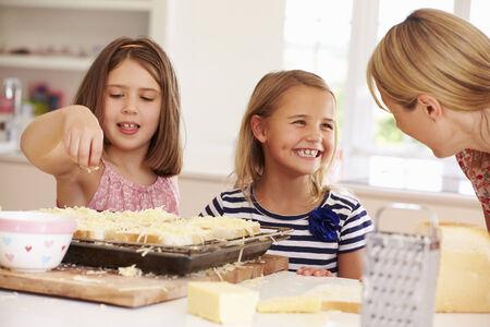comiendo pan: Muchachas con la madre Hacer queso en tostadas Foto de archivo