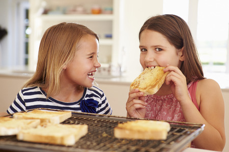 Two Girls Eating Cheese On Toast In Kitchen photo