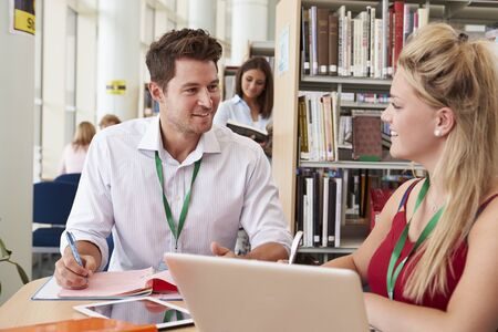 Teacher Helping College Student With Studies In Library