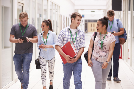Group Of College Students Walking Along Corridor