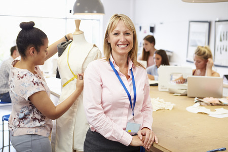 Portrait Of Teacher Helping College Fashion Students Imagens