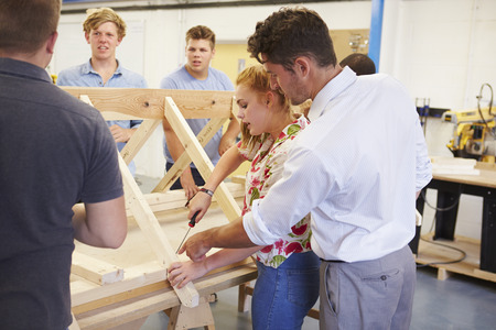 Teacher Helping College Students Studying Carpentry Stock Photo