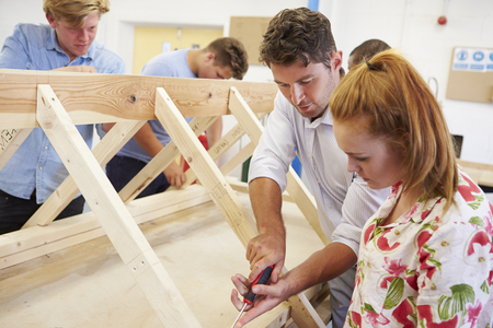 Teacher Helping College Students Studying Carpentry Imagens