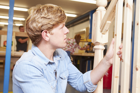 Student In Carpentry Class Working On Staircase