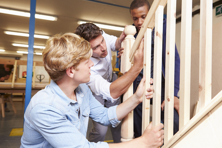 Students In Carpentry Class Working On Staircase