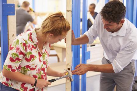 Teacher With Student In Carpentry Class Fitting Door Lock Imagens