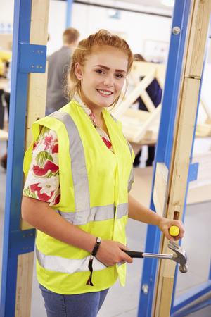 Female Student In Carpentry Class Fitting Door Lock