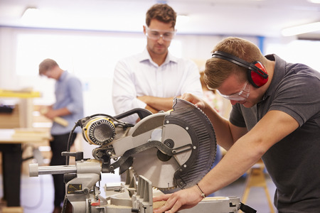 Student And Teacher In Carpentry Class Using Circular Saw Reklamní fotografie
