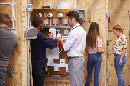 Teacher Helping Students Training To Be Electricians