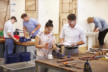 Teacher Helping College Students Studying Plumbing 写真素材