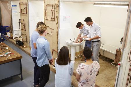 College Students Studying Plumbing Working On Washbasin