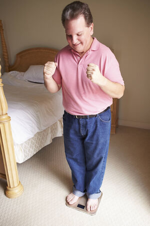 Happy Overweight Man Standing On Scales In Bedroom photo